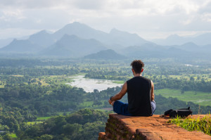 Young man meditating on the background of beautifil mountain landscape